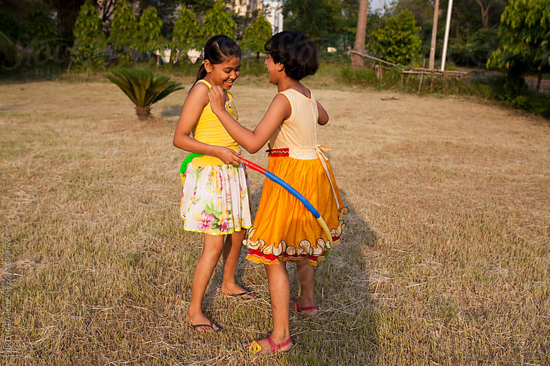 Teenage girls making fun with Hula Hoop by PARTHA PAL for Stocksy United