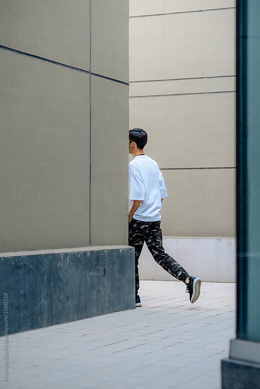 Young Chinese man leaving in the corner of building by MaaHoo Studio for Stocksy United