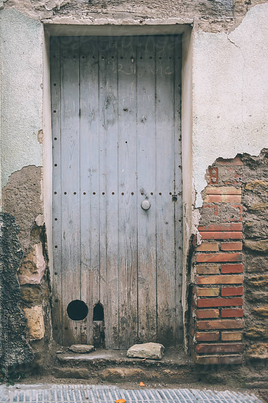 old blue door in abandoned town by Javier Pardina for Stocksy United