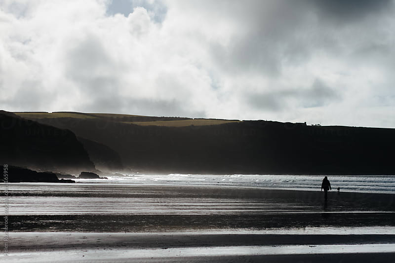 Silhouette of a dog and owner on a winter beach by Helen Rushbrook for Stocksy United