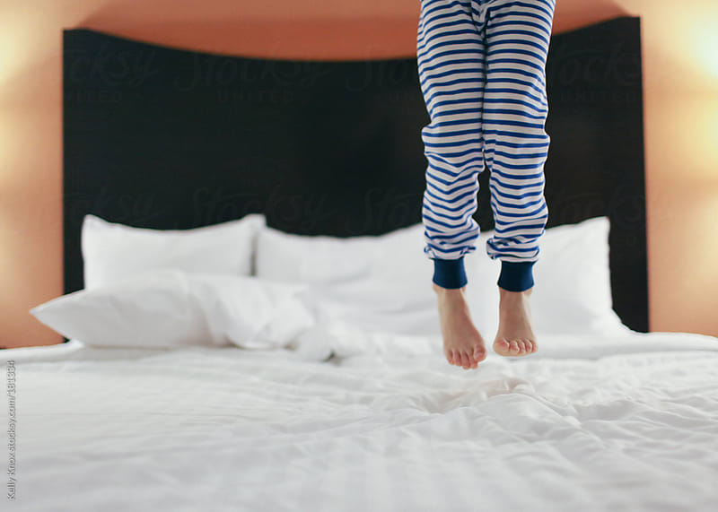 child jumping on a hotel bed by Kelly Knox for Stocksy United