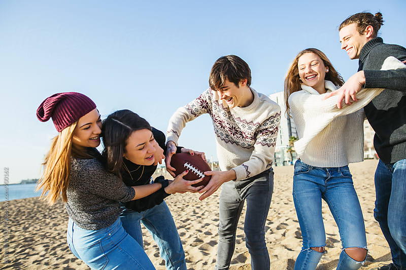Group of teenage friends playing football on the beach. by BONNINSTUDIO for Stocksy United