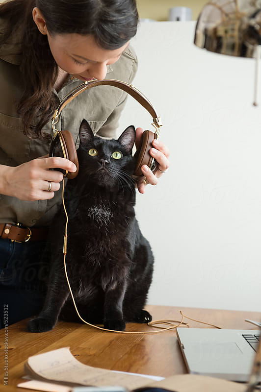 Woman giving headphones cat listen music by Milles Studio for Stocksy United