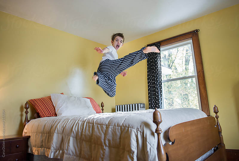 Child does a flying sidekick while jumping on his bed by Cara Dolan for Stocksy United