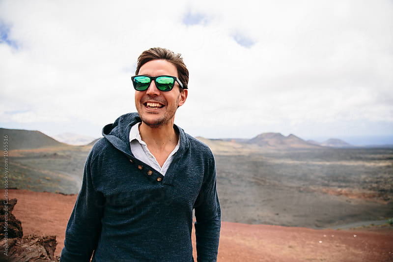 Portrait of smiling man with windy hair against of mountains by Alejandro Moreno de Carlos for Stocksy United