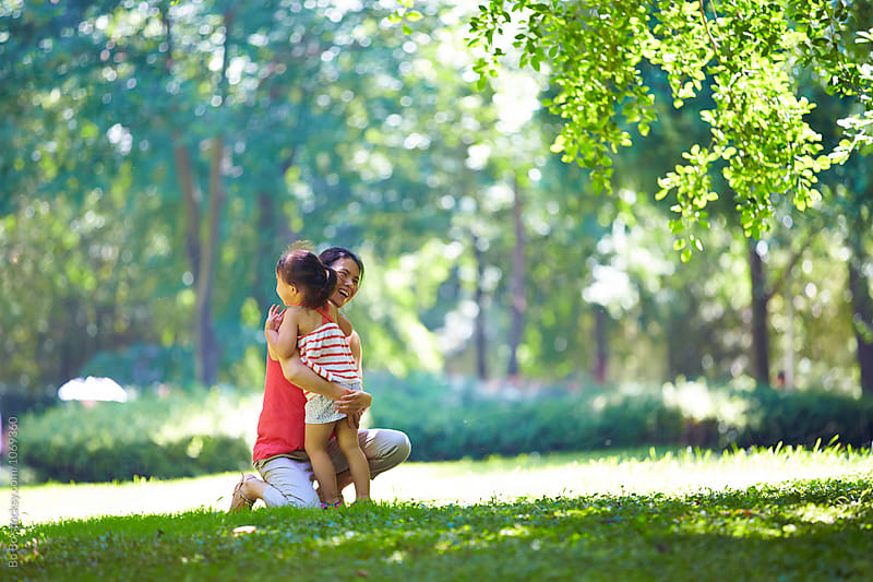 asian woman hug her little girl outdoor in the sunny park by Bo Bo for Stocksy United