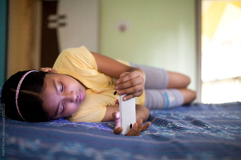 Teenage girl using smartphone  and lying over bed by PARTHA PAL for Stocksy United