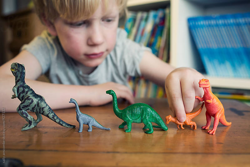 Child playing with toy dinosaurs by sally anscombe for Stocksy United