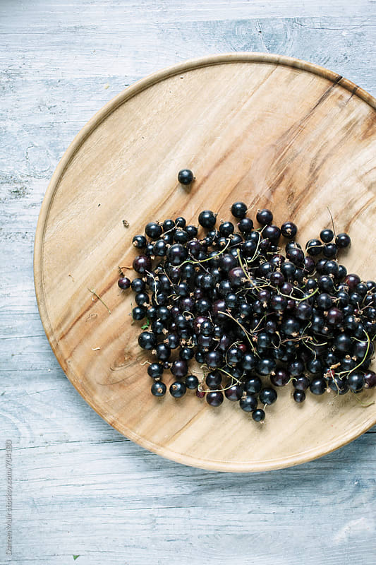 Fresh blackcurrants on a wooden plate. by Darren Muir for Stocksy United