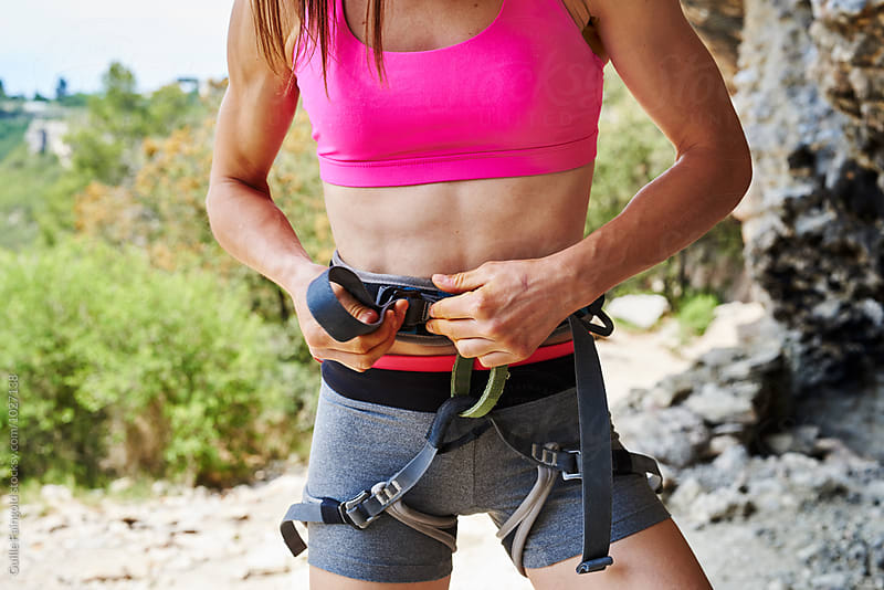 Close-up of sportswoman wearing safety belt before climbing by Guille Faingold for Stocksy United
