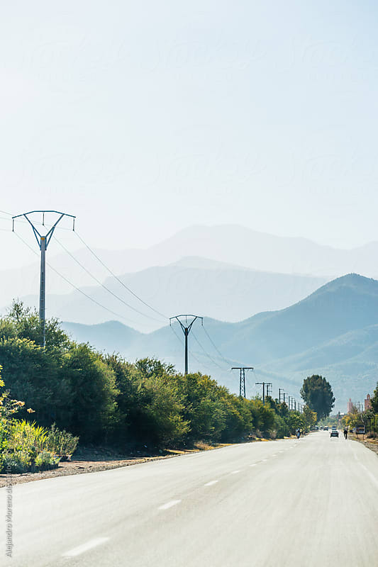 Road with mountains in the background and electric cables by Alejandro Moreno de Carlos for Stocksy United