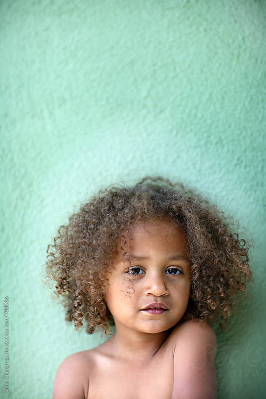 African American Child Standing Up Against a Green Wall by Dina Giangregorio for Stocksy United