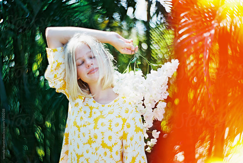girl in yellow dress with green palms with light leak by wendy laurel for Stocksy United
