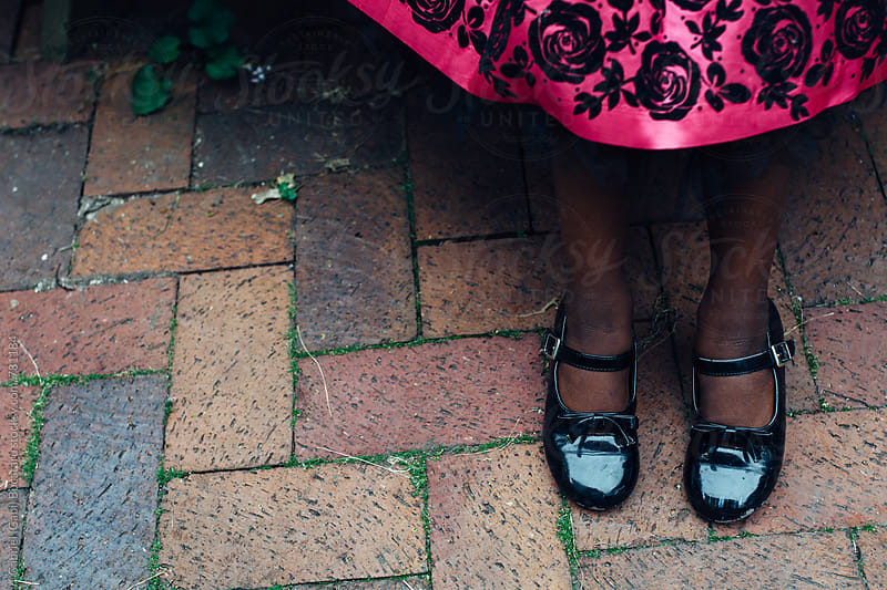 Black girl's feet in patent leather shoes and pink dress by Gabriel (Gabi) Bucataru for Stocksy United