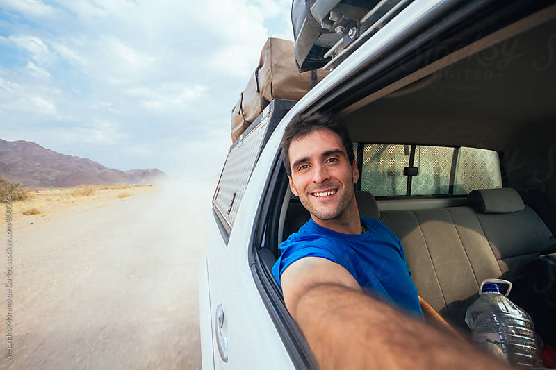 Young happy man taking a selfie from the passenger seat open window with views of the dusty gravel road and mountain scenery behind by Alejandro Moreno de Carlos for Stocksy United
