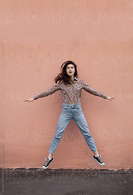Stylish teen girl jumping near wall    by Sergey Filimonov for Stocksy United