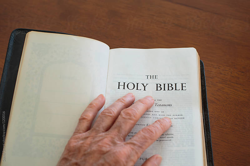 A hand resting on an open Bible by David Smart for Stocksy United