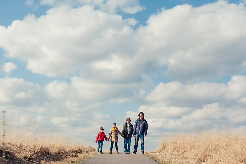 Four kids in different ages holding hands under a big sky by Cindy Prins for Stocksy United