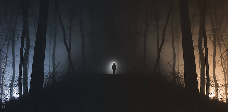 Man in surreal haunted forest on Halloween night by Cosma Andrei for Stocksy United