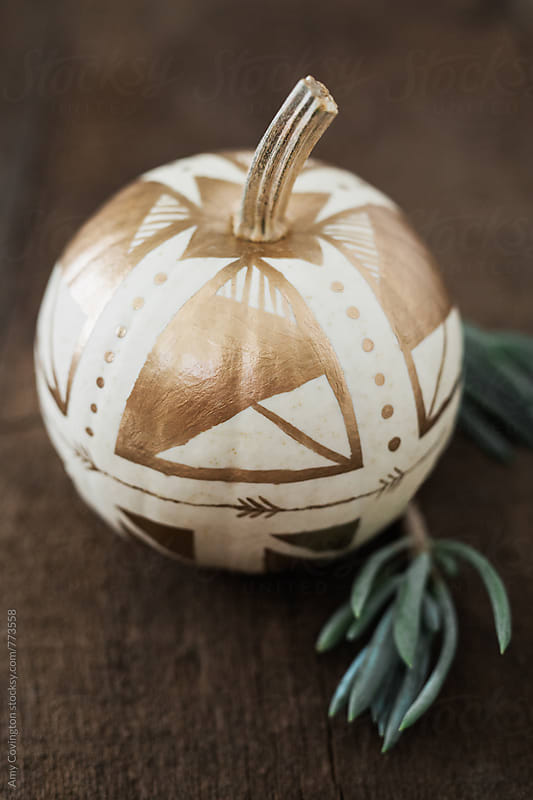 White pumpkin painted with gold geometric shapes by Amy Covington for Stocksy United