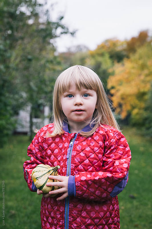 Little girl holding pumpkin for Halloween by Lior + Lone for Stocksy United