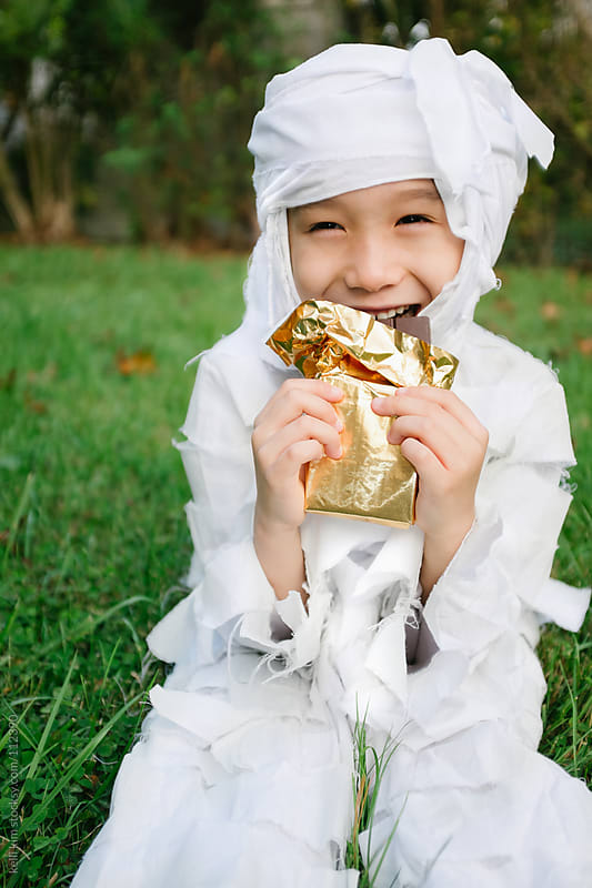 Young Mixed Race Boy In Mummy Costume Eats Candy Bar by Kelli Seeger Kim for Stocksy United