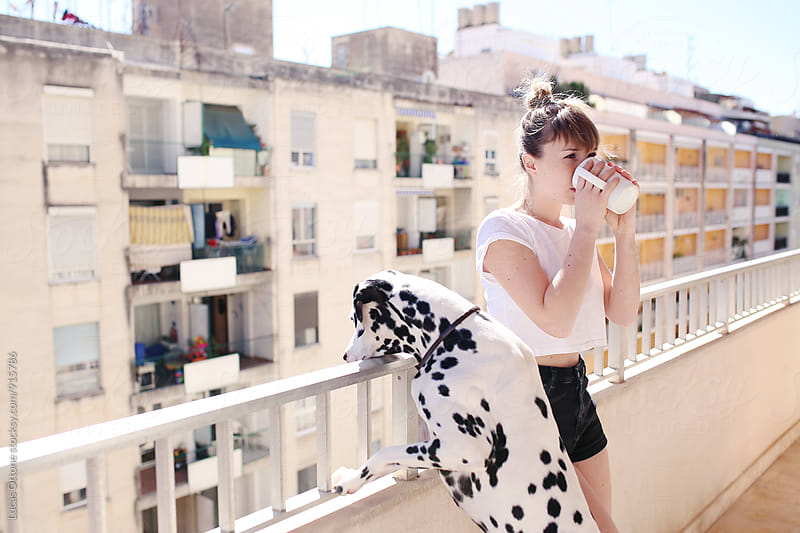 Girl drinking coffee with a dalmatian dog by Lucas Ottone for Stocksy United
