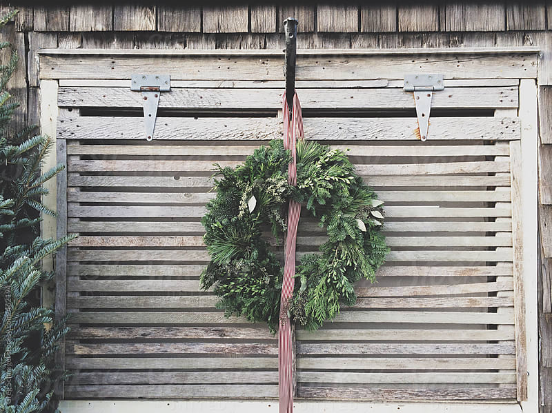 Christmas holiday wreath hanging on a barn door by Greg Schmigel for Stocksy United