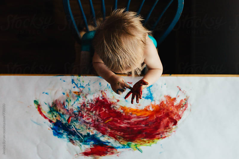 Small child fingerpainting on kitchen table by Jessica Byrum for Stocksy United