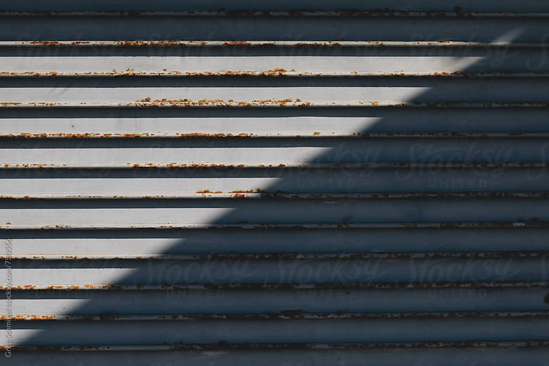 A metal rolling garage door with rust and sunlight and shadows by Greg Schmigel for Stocksy United
