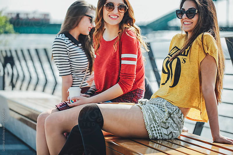 Three Girlfriends Relaxing Outdoors by Lumina for Stocksy United