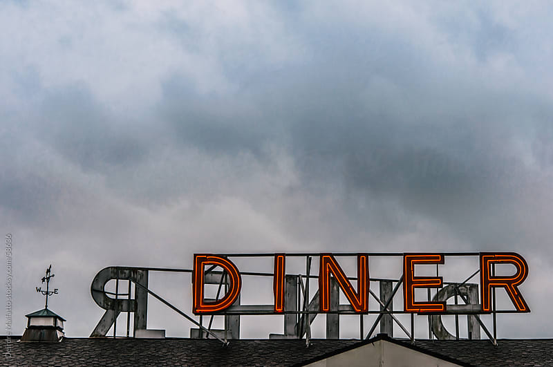 Red neon diner sign on a roof with clouds by Deirdre Malfatto for Stocksy United