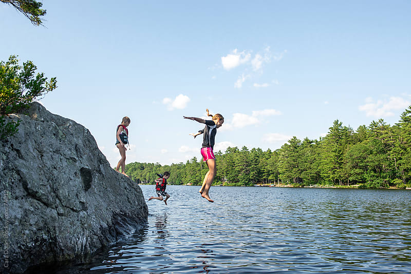 Three kids jump off a giant rock into a lake by Cara Slifka for Stocksy United