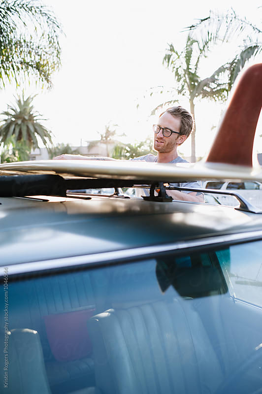 Man securing his surfboard on roof of car by Kristin Rogers Photography for Stocksy United