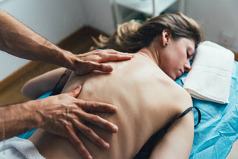Young woman lying on her front on a bed receiving a massage on her back by a male therapist by Inuk Studio for Stocksy United