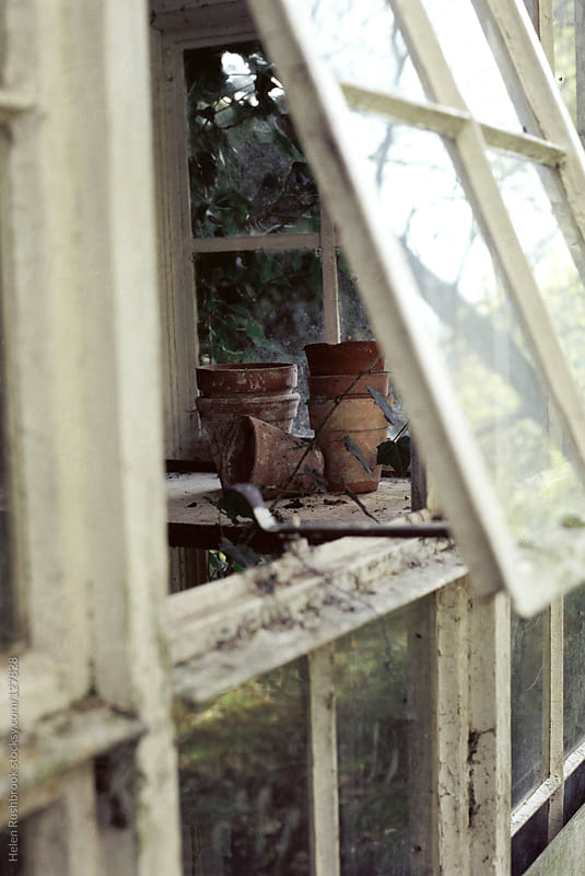 Vintage terracotta pots seen through the open window of a derelict greenhouse. by Helen Rushbrook for Stocksy United