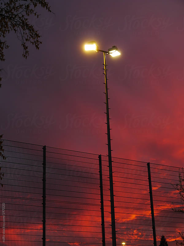 Streetlamps and fencing at sunset by rolfo for Stocksy United