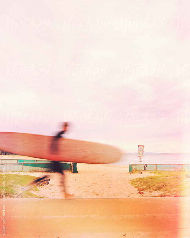 blurred surfer walking along a path at the beach by Gillian Vann for Stocksy United