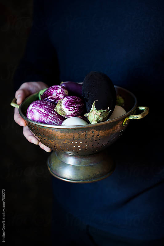 Person holding vintage colander with a variety of eggplants by Nadine Greeff for Stocksy United