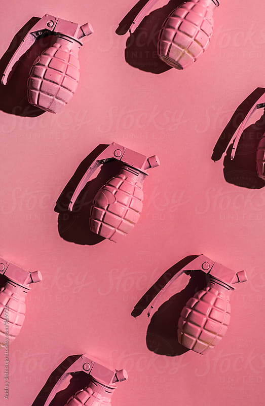 Pink hand grenades on pink background . by Audrey Shtecinjo for Stocksy United