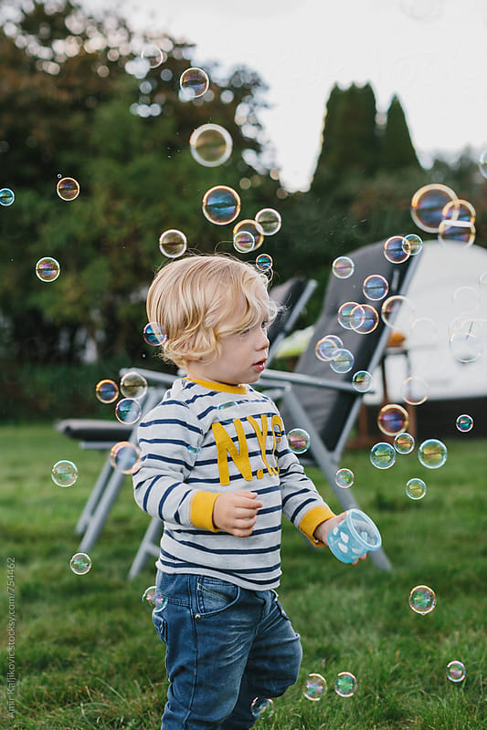 Little blond boy plays with bubbles by Amir Kaljikovic for Stocksy United