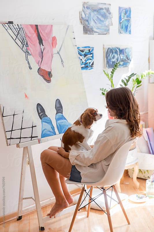 Artist taking a break to play with her puppy by Jovo Jovanovic for Stocksy United
