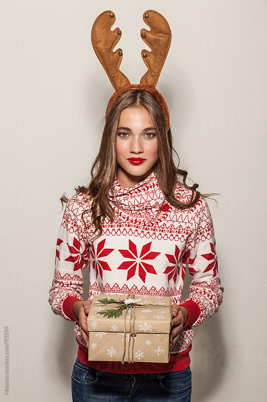Woman With Reindeer Horns Holding Christmas Gift by Mosuno for Stocksy United