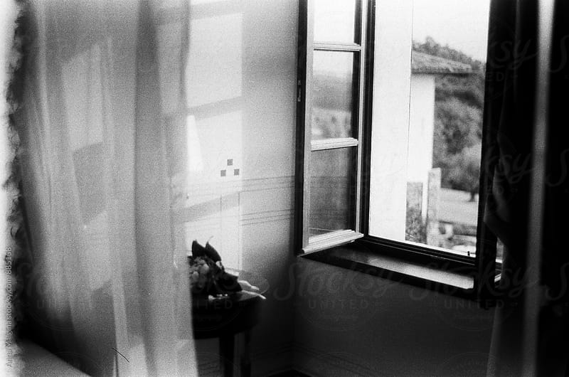 A black and white film photo of a window view from the hotel room by Anna Malgina for Stocksy United