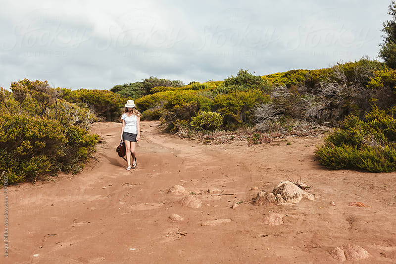 Teen girl, carrying a satchel, walks along a dirt track in the bush by Jacqui Miller for Stocksy United