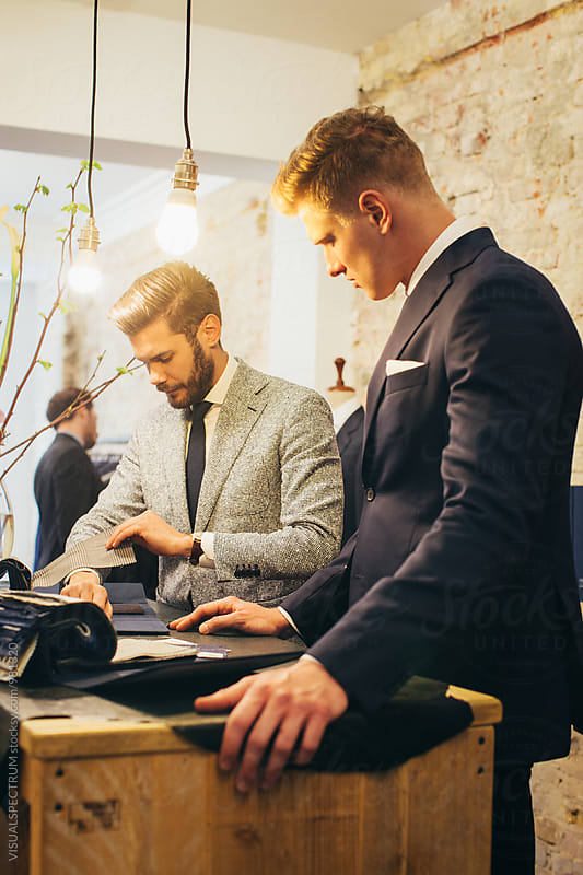 Men's Fashion - Two Stylish Young Caucasian Men in Suits Looking at Suit Fabrics by VISUALSPECTRUM for Stocksy United