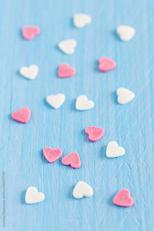 pink and white sugar heart shapes on blue background  by Corinna Gissemann for Stocksy United