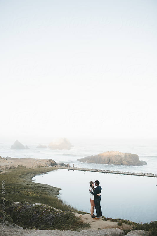 couple hugging in front of beautiful scenic coastline by Nicole Mason for Stocksy United