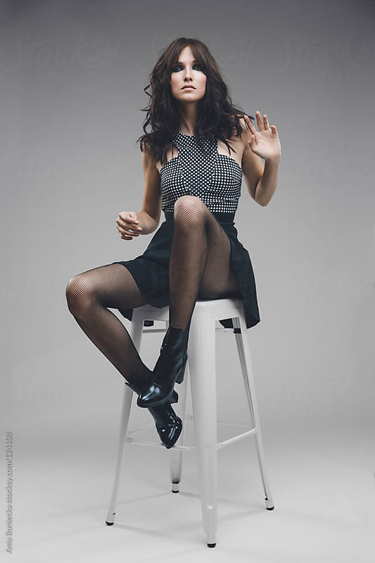 A model moving positions while seated on a studio stool by Ania Boniecka for Stocksy United