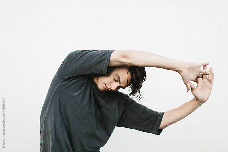 expressive portrait of man against white wall by Nicole Mason for Stocksy United